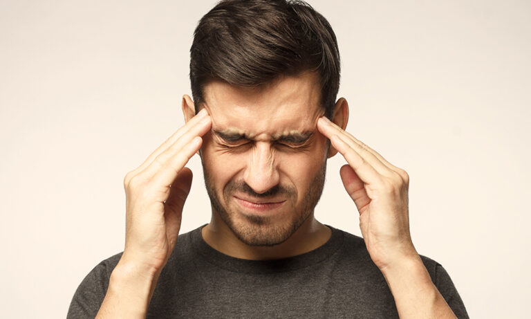 man rubs his temples and makes a painful face to cope with a headache.