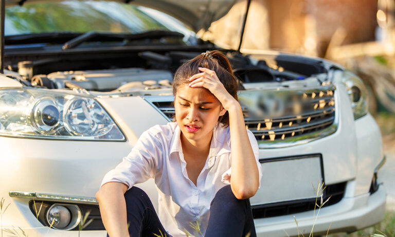 A young woman holds her head and sits in front of a crashed car.