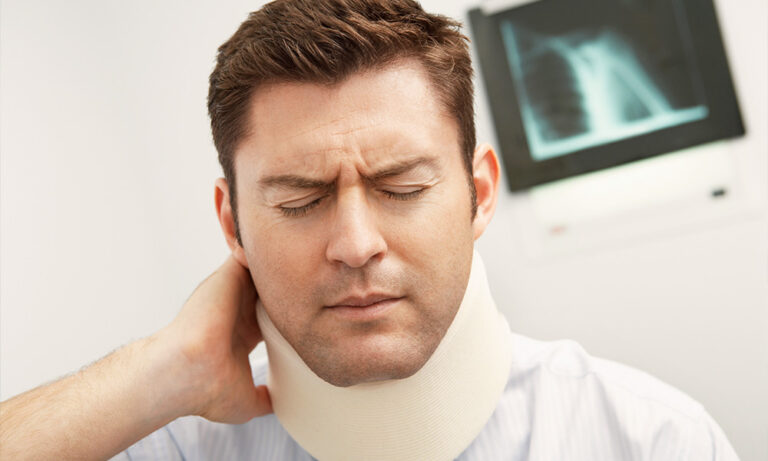Man with neck brace holding neck in hospital room.