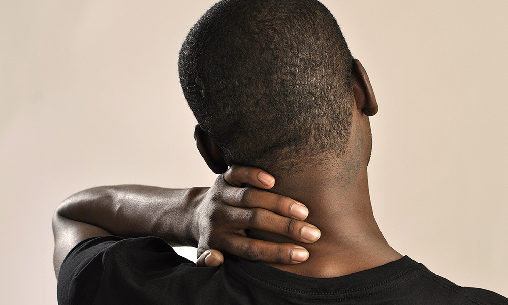 A man rubs the back of his neck while dealing with a whiplash headache.