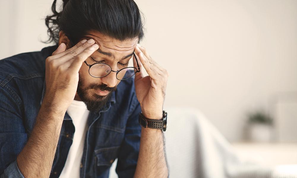 A man rubs his temples in a sign on headache pain.