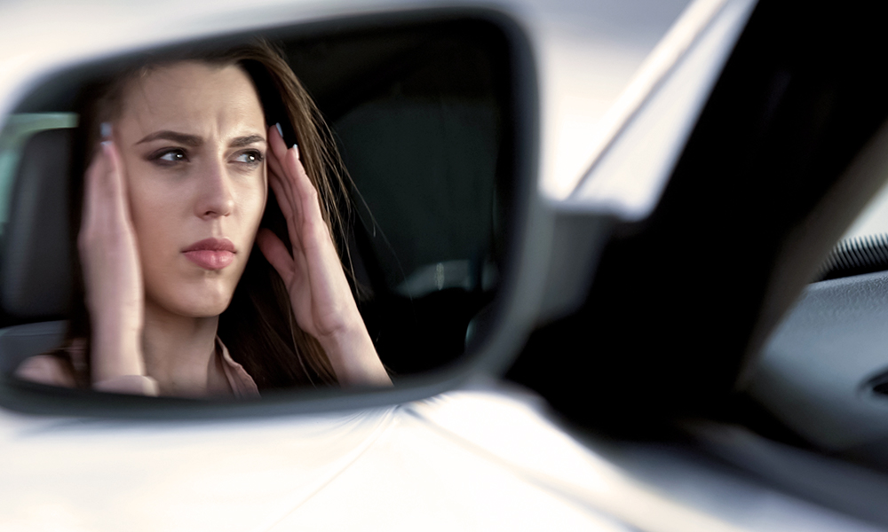 A photo of a woman rubbing the sides of her head to relieve headache while sitting in her car as viewed from the side mirror of the car.