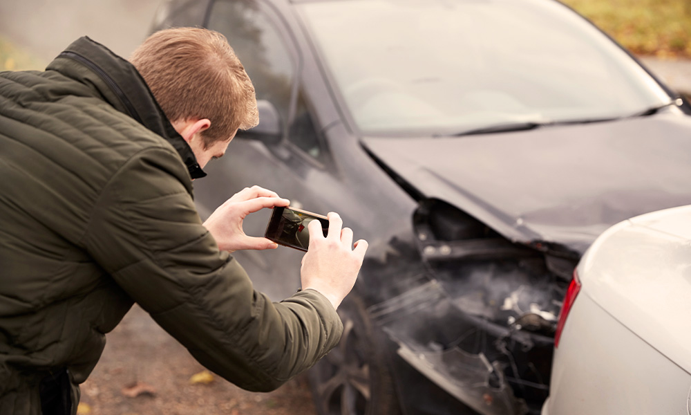 Man taking photos of damaged car after accident.