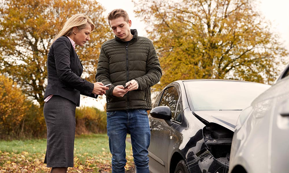 Woman and man exchanging information after car accident.