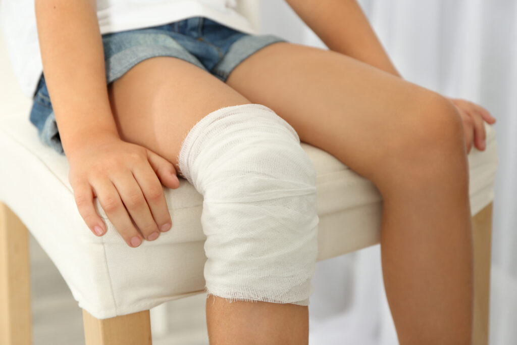 close up view little girl s knee with bandage 1