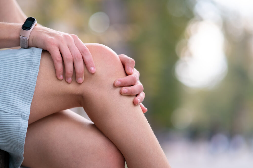 Close up of woman hands holding her knee in pain sitting.